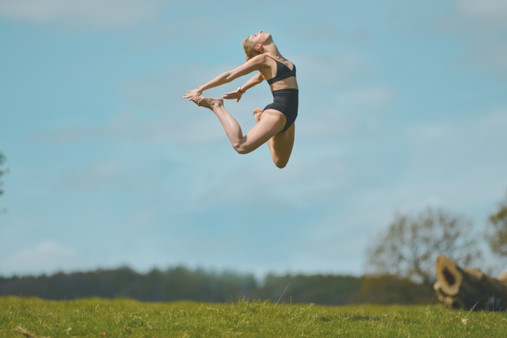 Girl Dancer Jumping For Joy In Field
